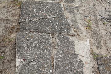 Obraz Stary, spękany, wybrzuszony chodnik z betonowych płyt. - fototapety do salonu