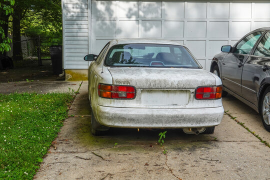 Rear view of an extremely dirty white car in a driveway in front of a white garage door