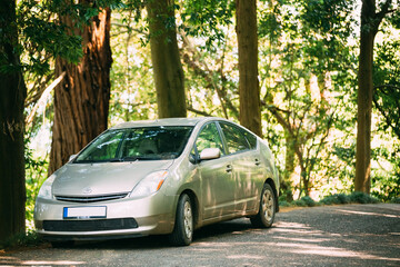 Toyota Prius is a full hybrid electric automobile car is parked on country road in forest in shadow of trees
