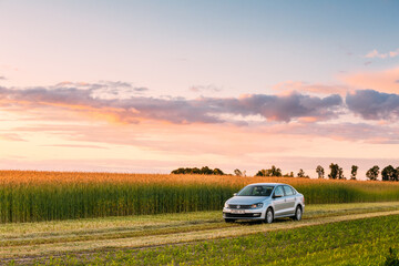 Volkswagen Polo Car Parking On Wheat Field. Sunset Sunrise Dramatic Sky On A Background In Sunny Evening.