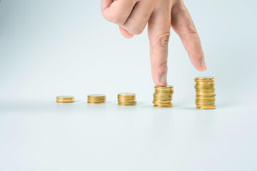 business and finance investment and saving activity with gold coin arrange on white isolated with finger acting background