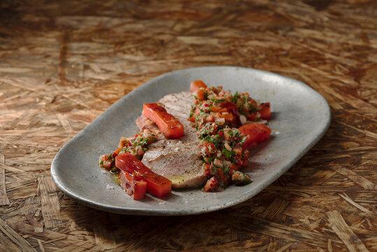 leichtes Grill Rezept mit Schwein, Wassermelone und Chimichurri auf Holztisch mit braunem Hintergrund