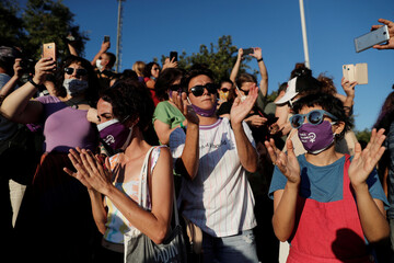Demonstrators applaud during a protest against femicide and domestic violence, in Istanbul