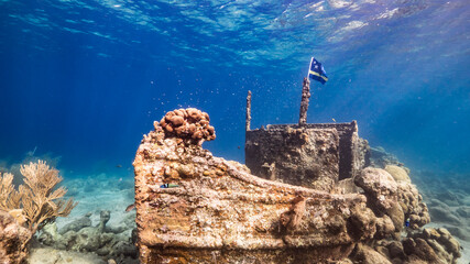 "Ship wreck ""Tugboat"" in  shallow water of coral reef in Caribbean sea with  Curacao Flag, view to surface and sunbeams"