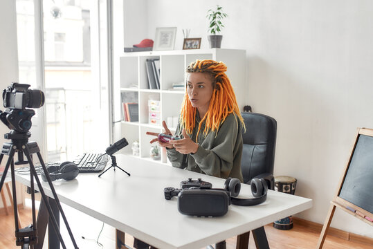 Female technology blogger with dreadlocks holding game controller joystick while recording video review of new gadgets using microphone at home