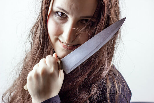 Young caucasian insane brunette woman with knife in black against light background. Halloween concept.