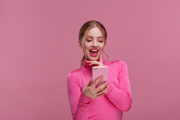 The best day ever. Surpised young redhead woman holding pink smartphone, smiling and expressing positivity. Happy girl got shocking positive news. Copy space. Young people working with mobile devices.