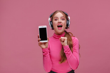 Funny open-eyed redhead girl showing blank screen mobile phone on camera. Young happy woman wearing earphones demonstrating smartphone display over pink background. Copy space. App for your business