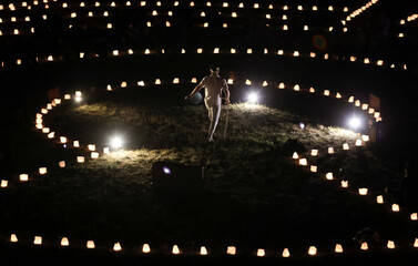 "An actor performs at the light installation of about 3500 candles ""The great journey. Dreams in the sea of light"" in Berlin"