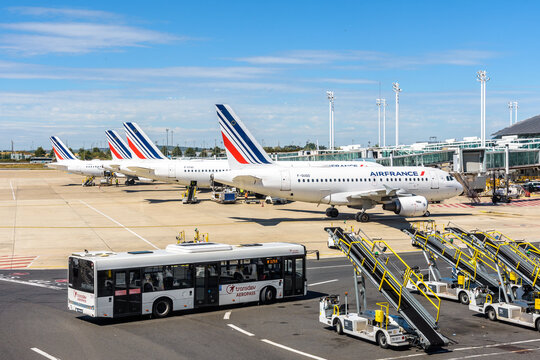 Roissy-en-France, France - July 27, 2020: A shuttle bus is driving on Paris-Charles de Gaulle Airport between belt loaders and Air France airliners stationing on the apron area by the Terminal 2F.