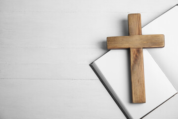 Christian cross and Bible on white wooden background, flat lay with space for text. Religion concept