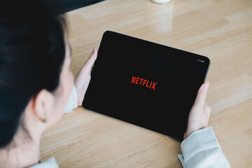 CHIANG MAI, THAILAND, JULY 26, 2020: Woman hand holding Smart tablet with Netflix logo on Apple iPad. Netflix is a global provider of streaming movies and TV series