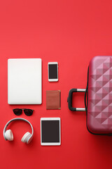 Packed suitcase with accessories and devices on color background. Travel concept