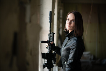 Concept of special force woman with a airsoft rifle on abandoned building background.