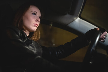 Pretty woman is driving a car at night close up.