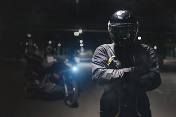 A motorbiker is standing with crossed hands on a dark parking.