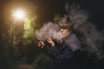Detective agent in a black leather hat with a gun in hand is smoking a smoming pipe in night park.