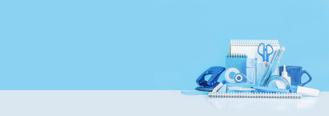 Group of various office supplies and school white and blue stationery on desk. Blue background...