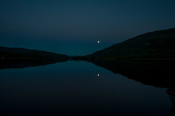 Night in the mountains. The moon reflected on a lake