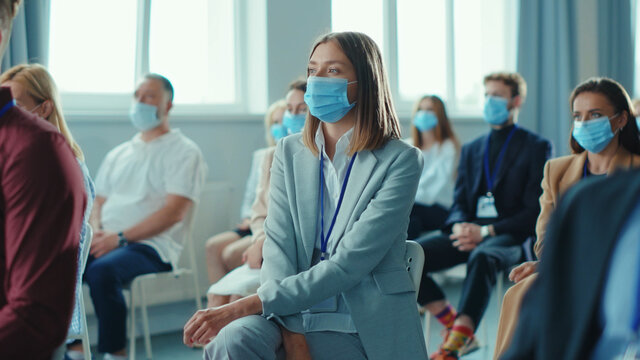 Diverse group of business persons wearing protective masks and listening to speaker lecturer at corporate seminar conference meeting. Pandemic outbreak. Workspace.