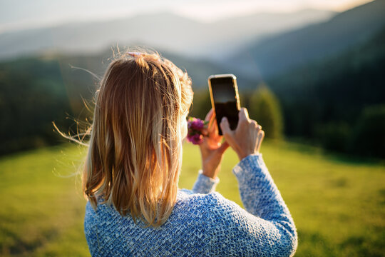 Young woman traveler take photo of beautiful sundown in mounting with mobile phone camera. Focused on sun glare girl's hair