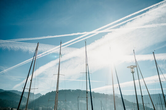 Low angle shot of boat masts under the sky with jet trials