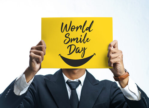 Businessman Holding World Smile Day Yellow Poster Covering His Face on White Background
