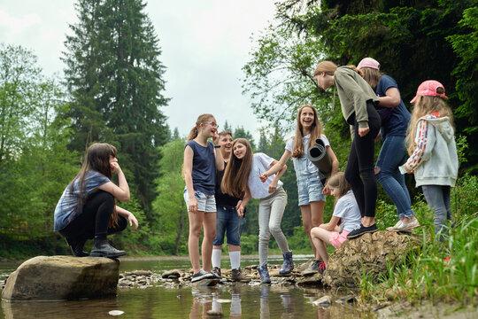 Teenage friends having fun on river beach.