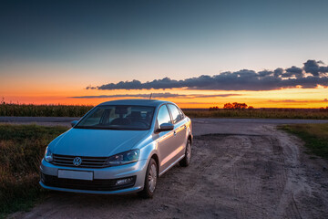 Volkswagen Polo Car Parking On A Roadside Of Country Road During Sunset Or Sunrise