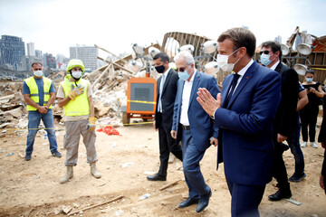 French President Emmanuel Macron gestures as he arrives at the devastated site of the explosion at the port of Beirut