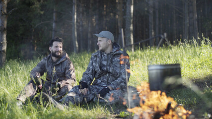 Two young man hunters or tourists near forest. Summer vacation forest. Friends sit at forest...