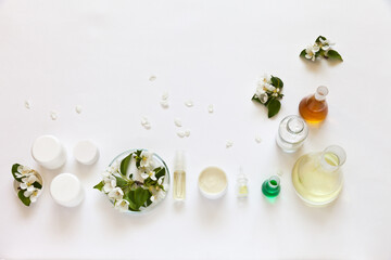Use of natural flower extracts to create new types of hypoallergenic cosmetics. Jars of face and hand creams on laboratory table with chemical glassware. Apple flowers, white background, copy space