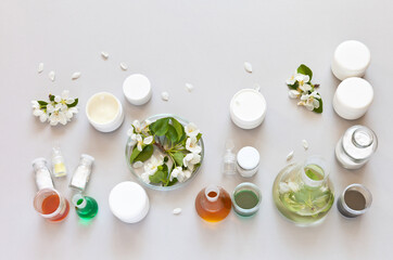 Natural cosmetics with floral extract. Jars of flower creams on a laboratory table with chemical glassware. Development of new types of cosmetics and testing of finished products. Flat lay, copy space