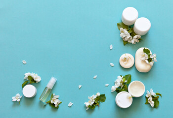 Natural cosmetics for face and hands with apple extract. White jars of cream, bars of soap and anti-aging mousse on a green background with apple flowers. Flat lay, copy space