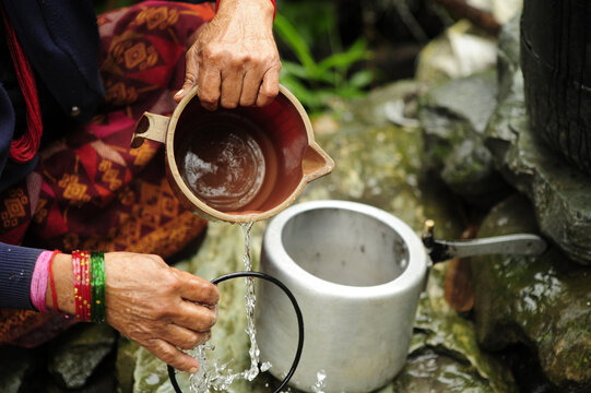 Close up shot of a person washing a metal circle with water in the nature of Nepal