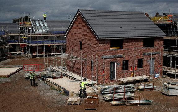 Builders work on a new Barratt Homes housing development near Warrington, Britain