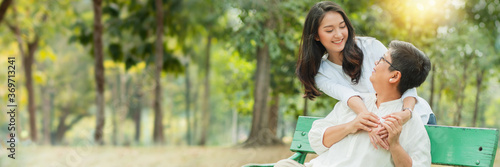 Mother and daughter hug and smiled together on chair in garden, concept of mother day and happiness family