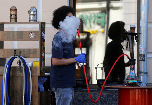 A man smokes a hookah in a cafe in Kyiv