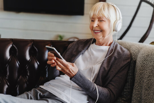 Happy senior woman in headphones listening music at home