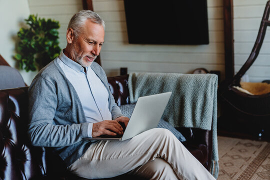 Handsome old man using laptop and smiling while sitting on couch at home