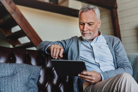 Mature caucasian man websurfing on digital tablet at home