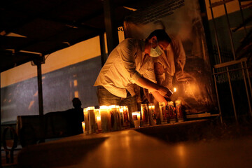 A man lights up a votive candle while family and friends of Diana Armida pray outside the General Hospital for her recovery as she is hospitalized due to the coronavirus disease (COVID-19), in Ciudad Juarez
