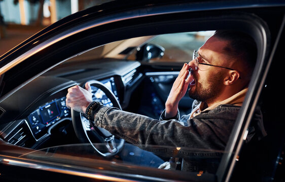 Tired handsome unshaved man in fashionable clothes riding his automobile