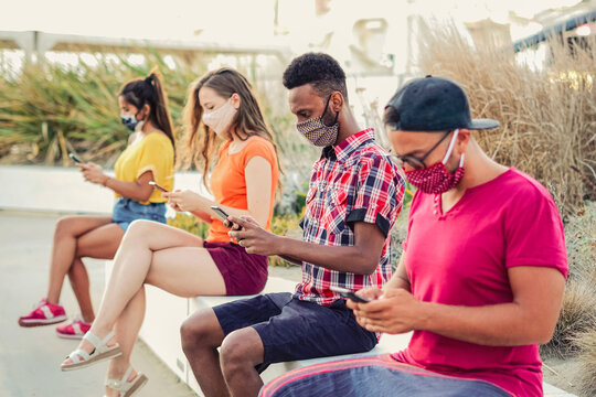 Friends using their smartphones in covid 19 times protected with face mask - Young people using mobile device in distance outdoors