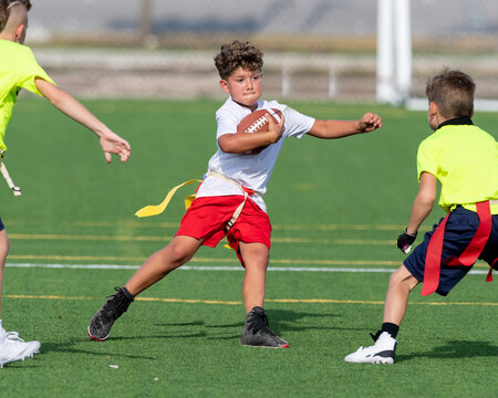Cute athletic little boy playing excitedly in a flag football game