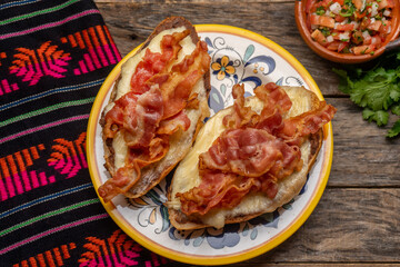 Mexican molletes with bacon and pico de gallo sauce on wooden background