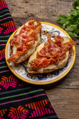 Mexican molletes with bacon on wooden background