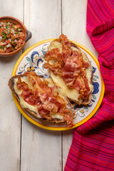 Mexican molletes with bacon and pico de gallo sauce on white background