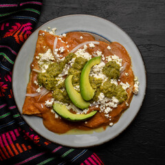 Mexican enfrijoladas with green sauce on dark background