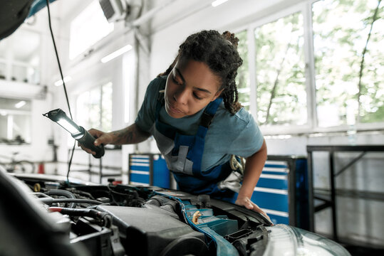 Moments of caring. Young african american woman, professional female mechanic looking, examining under hood of car with torch at auto repair shop